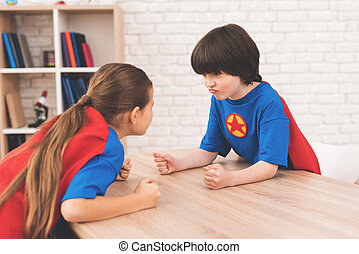A little girl and a little boy in suits of superheroes. They measure their strength in a bright room