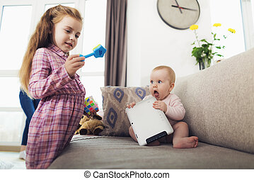 A little girl and an infant are playing. The girl holding a toy in her hands, the baby has just played with the tablet.