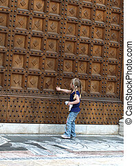 A little girl at the door of the Baptistery in Siena