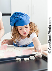 A little girl  baking with her grandmother
