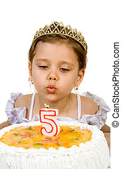 A little girl blowing out the candles on her birthday cake. Birthday cake celebrating five years.