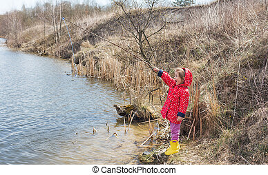 A little girl catches a fish. A lonely happy little child is fishing from the beach of a lake or pond.Photo of children pulling a fishing rod during a weekend fishing trip.