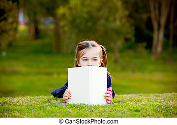 A little girl comtemplating her reading outside.