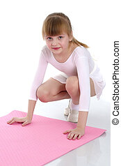 A little girl does gymnastic exercises.