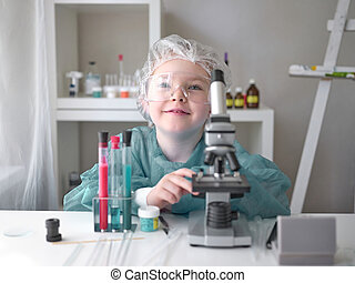 A little girl does scientific work in her home laboratory. The concept is the children of the future.