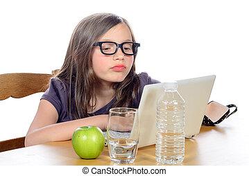 a little girl doing her homework on her computer on white