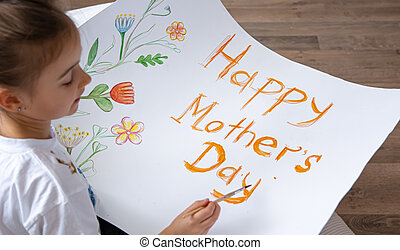 Little girl paints greeting card for Mom on Mother's Day with the inscription Happy mother's day.
