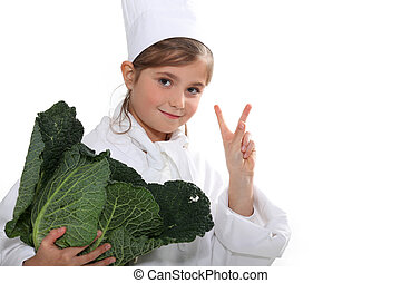 a little girl dressed in cook uniform holding a cabbage and doing the v sign