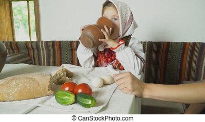 a little girl drinks milk from a jug