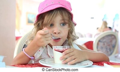 A little girl eat yogurt with jam - A little girl with curly...
