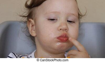 A little girl eats an orange. The concept of vegetarianism...
