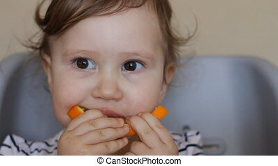 A little girl eats an orange. The concept of vegetarianism