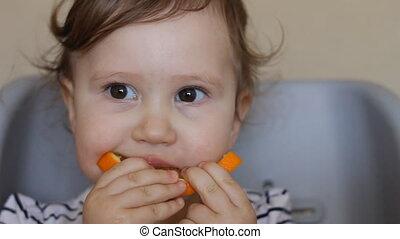 A little girl eats an orange. The concept of vegetarianism