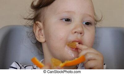 A little girl eats an orange.