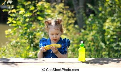 A little girl eats corn and drinks lemonade. Picnic