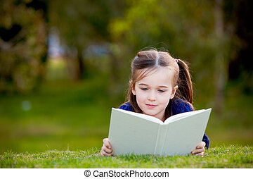 A little girl enjoying reading outdoors on the grass