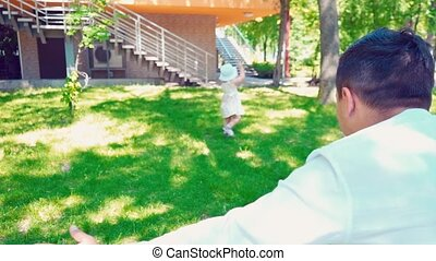 A little girl goes to the daddy on the green grass, turns in one place and falls, a fun family pastime, father and daughter