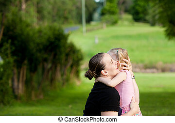 A little girl hugs and embraces her mother outdoors