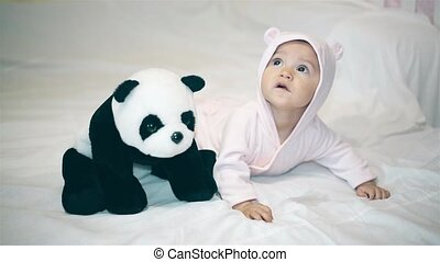 A little girl in a bear costume playing with a Panda on the bed