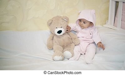 A little girl in a bear costume sitting next to a Teddy bear