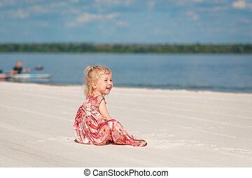 A little girl in a beautiful sarafna plays in the sand on the beach
