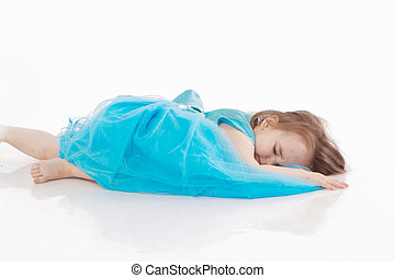 a little girl in a blue dress lying on the white floor