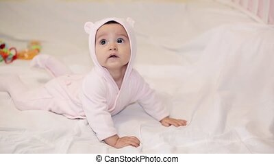 A little girl in a pink bear costume lying on a white blanket