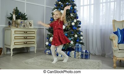 a little girl in a red dress is dancing near a Christmas tree