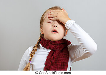 A little girl in a scarf is suffering from an illness. The child holds on to his head. The concept of the season of colds