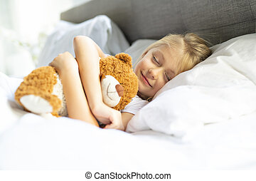 A little girl in bed sleeping and dreaming with teddy bear,