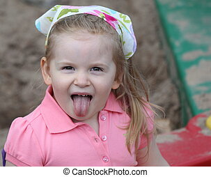 A little girl in sandbox sticking tongue out. - A cute...