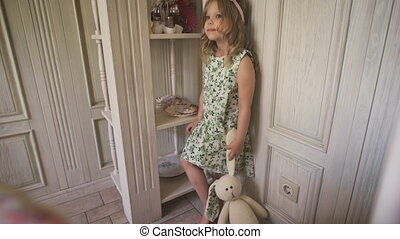 Childhood. A little pretty blonde girl in the dress looks thoughtfully standing the bright room. A little curly blondie is thinking about life.