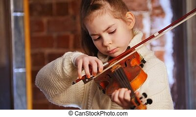 A little girl in white sweater learning how to play violin....