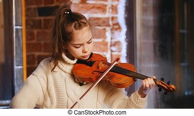 A little girl in white sweater playing violin. Portrait