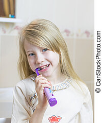 A little girl is brushing her teeth with an electric toothbrush.