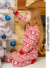 A little girl is decorating a Christmas tree.