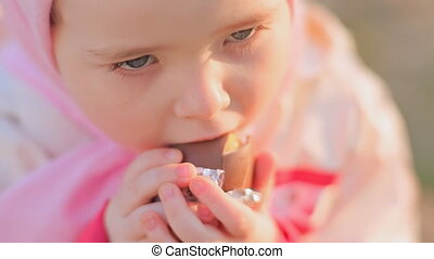 A little girl is eating a chocolate egg with a toy inside.