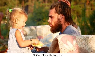 A little girl is feeding her dad with a spoon. Summer evening in the village.