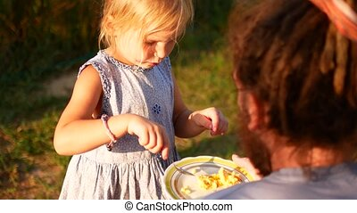 A little girl is feeding her dad with a spoon. Summer evening in the village