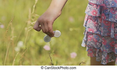 A little girl is holding a spinner.