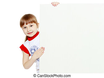 A little girl is looking from behind an empty banner.