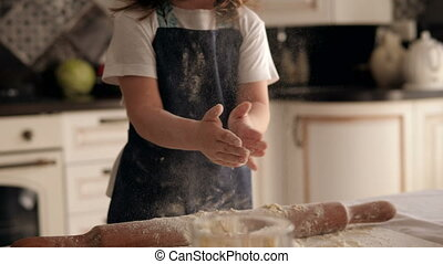 A little girl is playing with flour and dough in the kitchen, she claps her hands