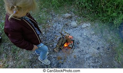 A little girl is preparing bread at the stake. Child near...