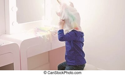 A little girl is sitting by the mirror in the nursery.