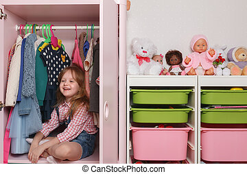 A little girl is sitting in a wardrobe with a children's department. Storage system for children's things