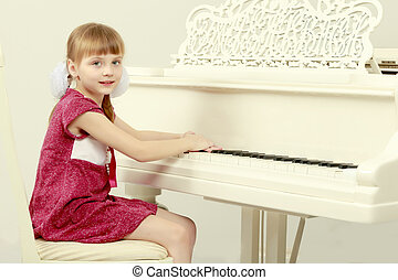 A little girl is sitting in front of a white grand piano.