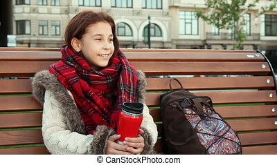 A little girl is sitting on a bench in a big city