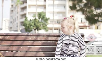 A little girl is sitting on a bench in the city