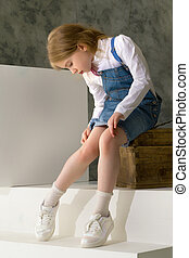 A little girl is sitting on a wooden box.