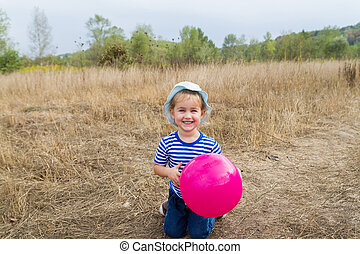 A little girl is sitting with a pink ball